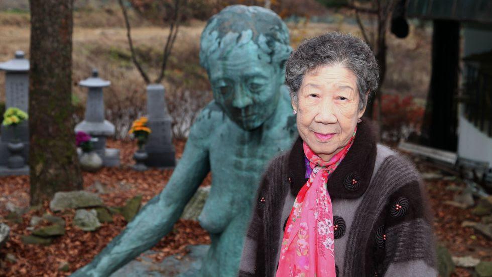 """Il-chul frente a la obra """"Mujer de la tierra"""", del artista Ok-Sang Im, concebida para recordar los crímenes contra las mujeres de confort."""