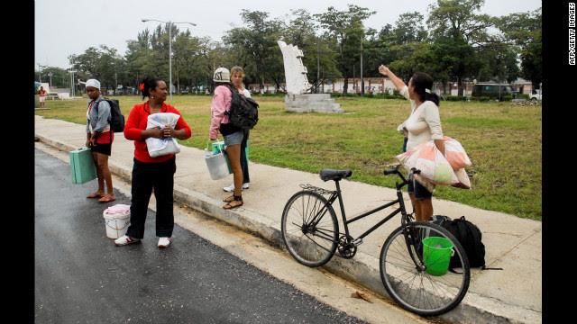 Citizens of Bayamo talk on the sidewalk on Wednesday.