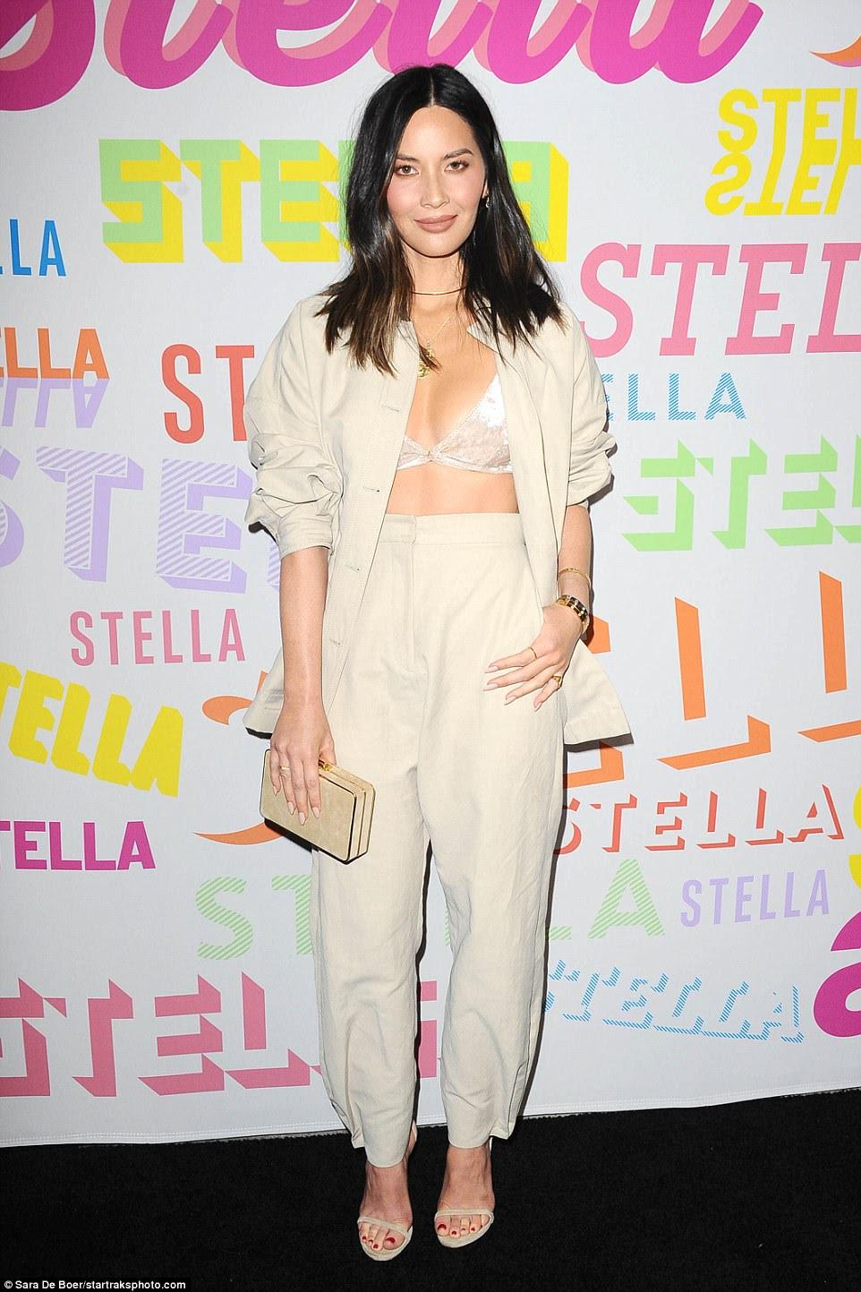 Maravilha em branco: Olivia Munn olhou em forma fina enquanto ela exibia seus abs abstratos em uma bralette branca junto com calças brancas fluidas