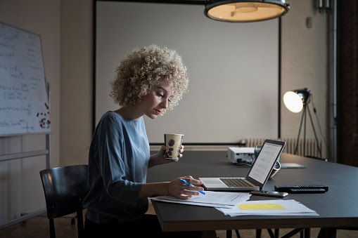 Woman working on laptop and documents in office : Stock Photo