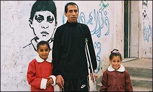 Yamal y sus dos hijas, con la imagen de Mohamed en el fondo.