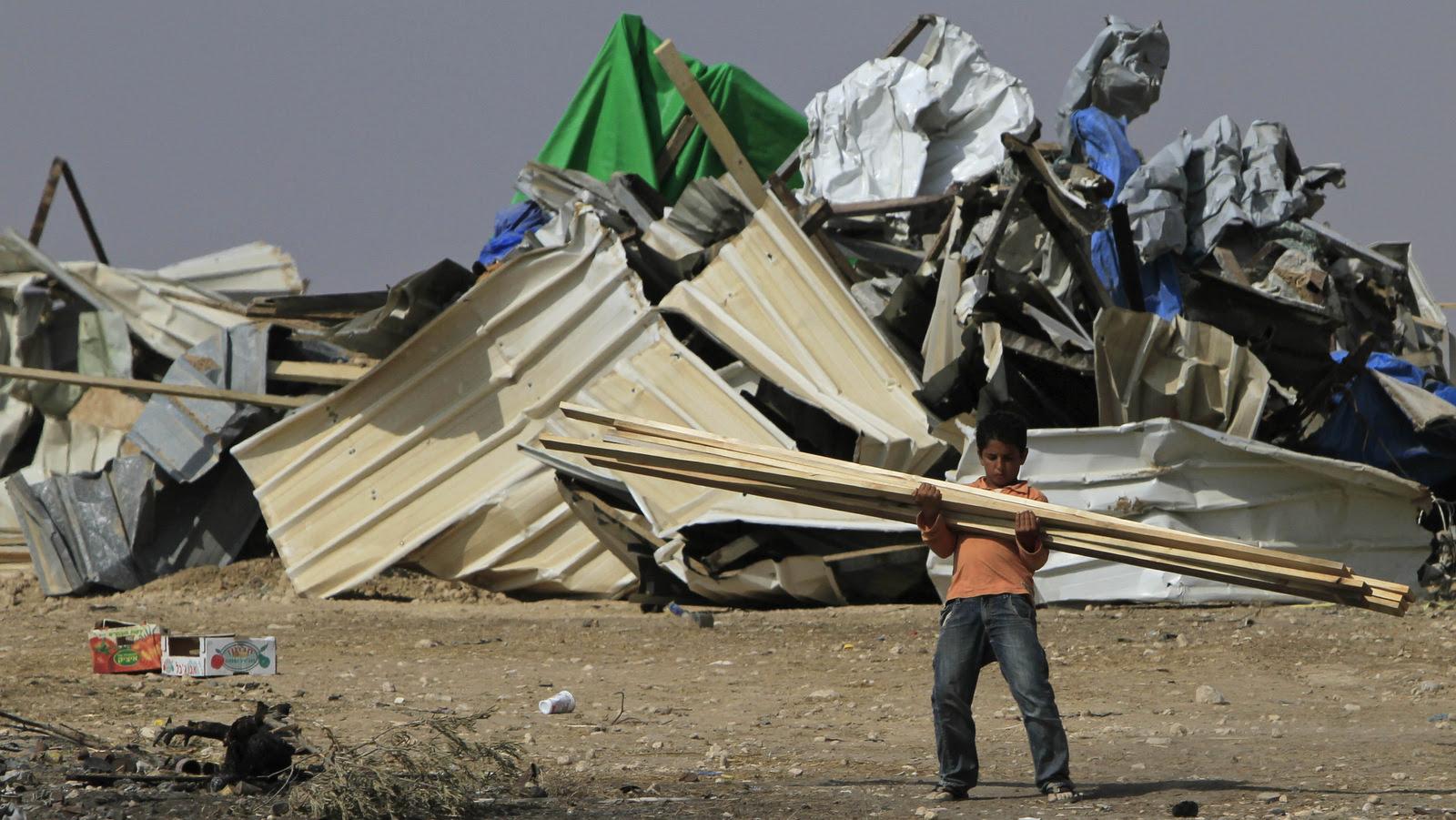 Um menino beduíno carrega madeira depois de demolir sua casa na vila de El Araqib, perto da cidade israelense do sul de Beersheba em 2010. (AP / Tsafrir Abayov)