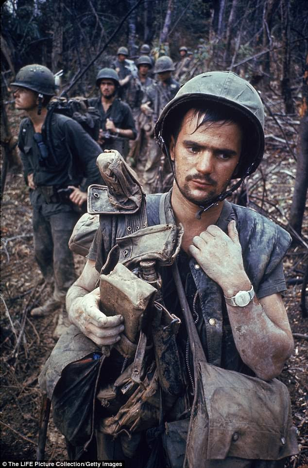 An exhausted looking US Marine on patrol with his squad  during the Vietnam War