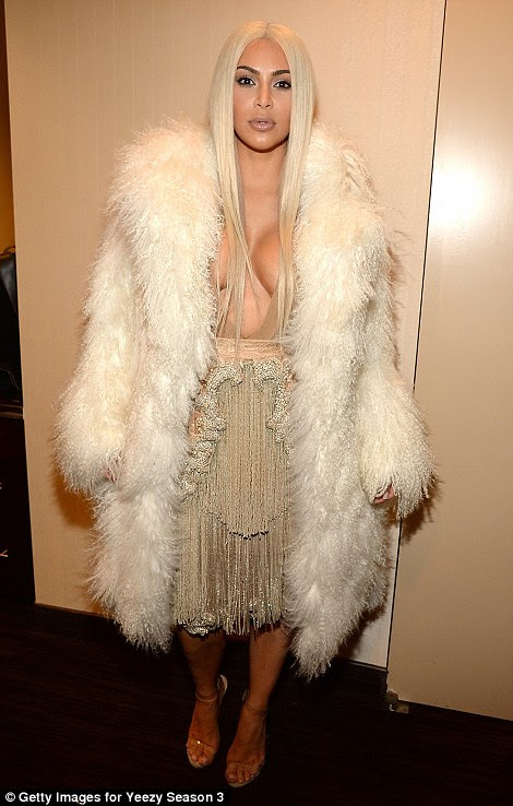 By his side: Kim put her ample assets on display in one of her husband's designs, but covered up against the chilly New York weather with a large furry coat