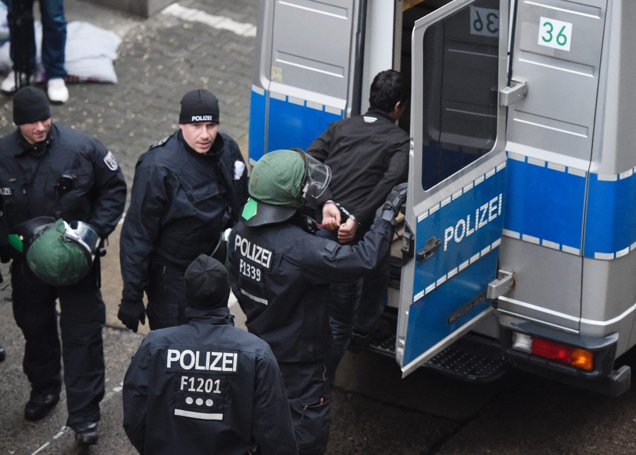 Police march off a handcuffed migrant (ODD ANDERSEN/AFP/Getty Images)