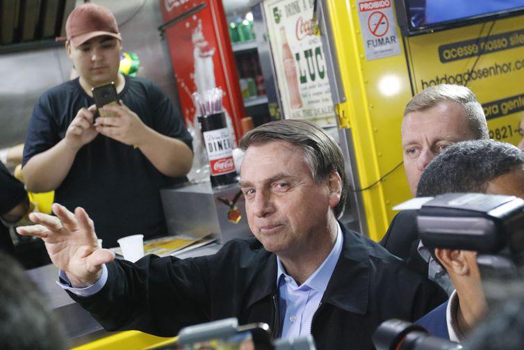 O presidente da República, Jair Bolsonaro, come cachorro-quente no food truck Hot Dog do Senhor, em visita à cidade de Resende.