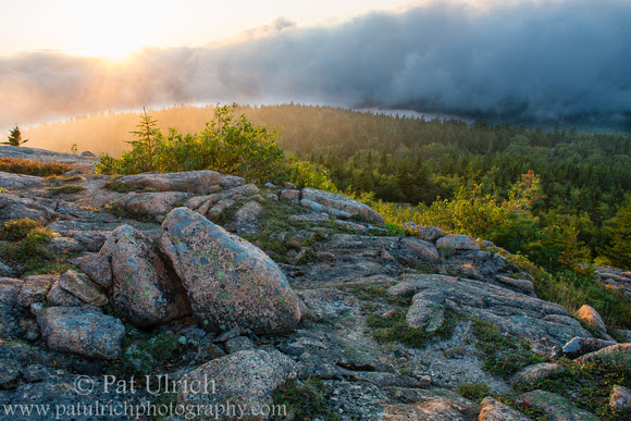 Photograph of the sun slipping behind the fog in Acadia National Park