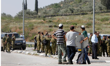 Jewish settler youths look at Israeli security forces