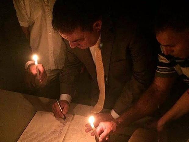 Prefeito de Curral de Cima precisou da ajuda de correligionários para assinar a posse à luz de velas (Foto: Totó Ribeiro/Arquivo Pessoal )