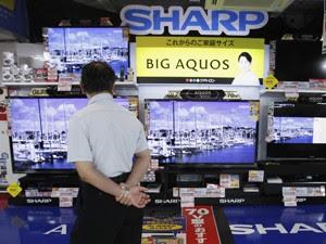 Homem observa televisores da Sharp em uma loja de eletrônicos em Tóquio (Foto: Reuters)