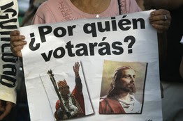 At a rally against Bolivia's proposed new constitution in Santa Cruz on Thursday, a woman carries a sign that pits President Evo Morales against Jesus Christ, asking, 'Who Will You Vote For?'