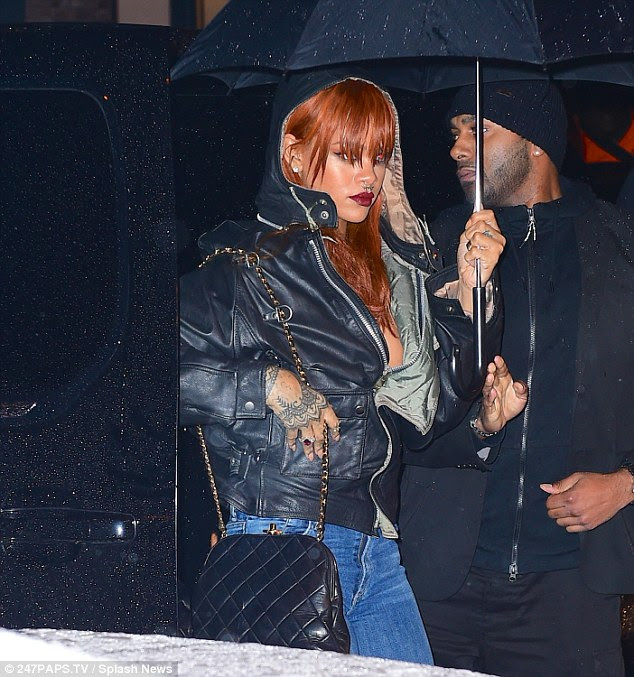 Taking care: Making sure her flame-red locks, complete with bangs were protective, she at points, kept the hoof of her jacket up as she made her way inside the venue