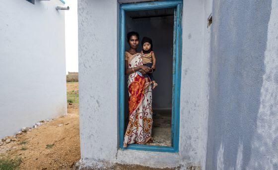 Una mujer y su bebé posan junto a su nueva letrina en Anantapur, India.