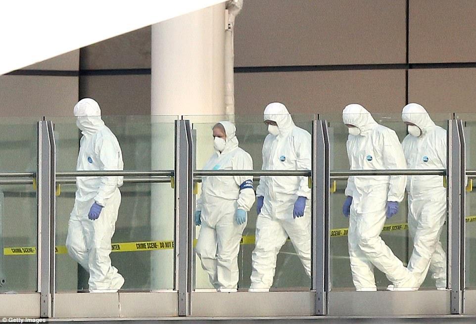 Oficiais forenses surgem depois de inspecionar a horrível cena em que um homem-bomba matou 22 pessoas quando saíram de um show pop na arena de Manchester na noite passada