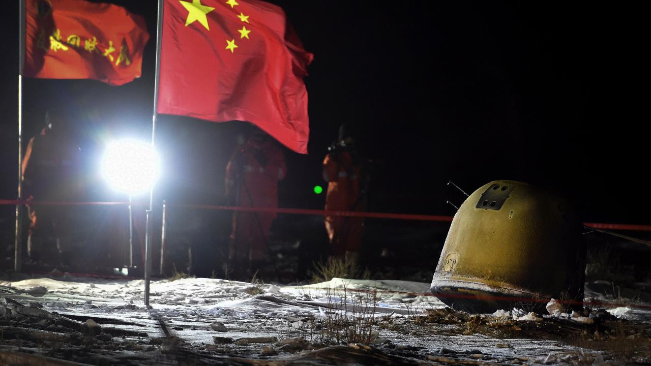 In this photo released by Xinhua News Agency, crew members film the capsule of the Chang'e 5 probe after its successful landed in Siziwang Banner, north China's Inner Mongolia Autonomous Region on Thursday, Dec. 17, 2020. A Chinese lunar capsule returned to Earth on Thursday with the first fresh samples of rock and debris from the moon in more than 40 years. (Ren Junchuan/Xinhua via AP)