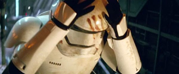 Finn is about to remove his bloodied Stormtrooper helmet in STAR WARS: THE FORCE AWAKENS.