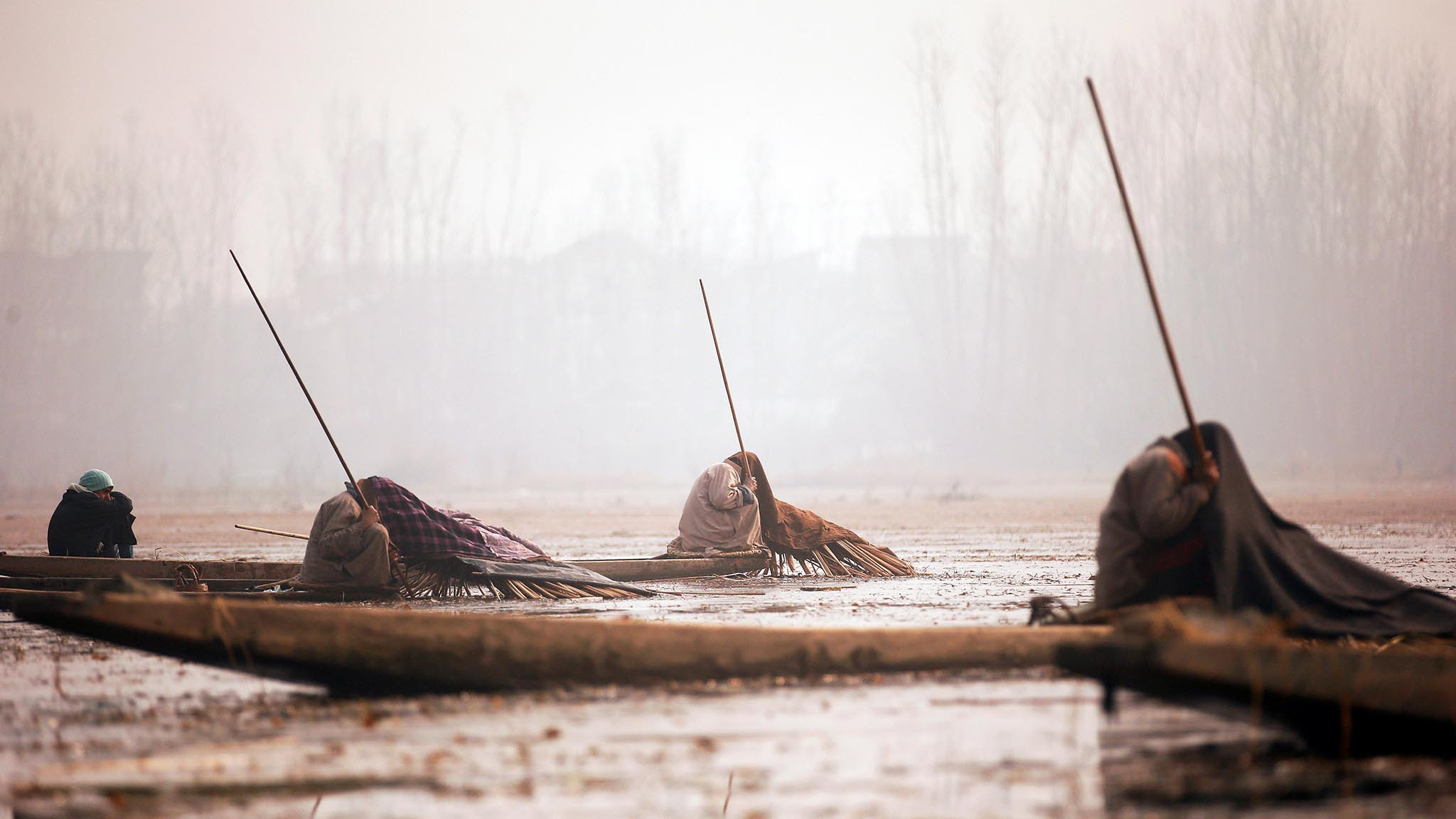 Kashmiri fishermen cover their heads and part of their boats with blankets and straw as they wait to catch fish in the waters of the Anchar Lake on a cold day in Srinagar