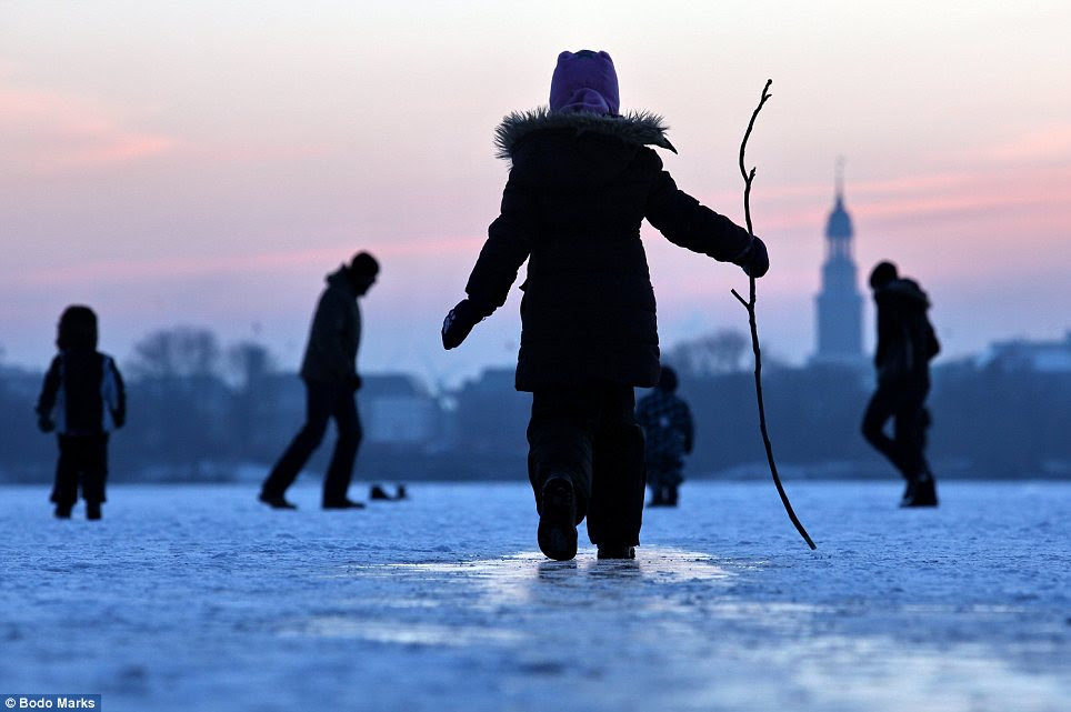 Play time: Children and adults stroll on a frozen lake in Hamburg, Germany, despite warnings not to do so from national officials