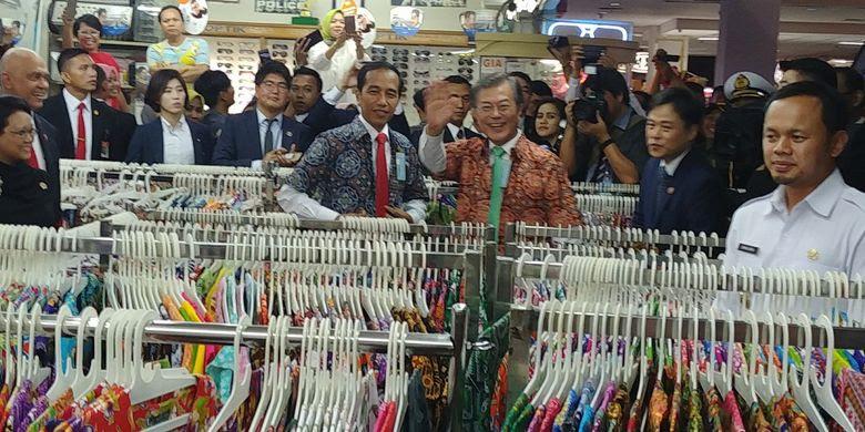 Presiden Joko Widodo dan Presiden Korsel Moon J   ae-in menjajal batik di salah satu toko di Bogor Trade Mall di Bogor, Jawa Barat, Kamis (9/11/2017).