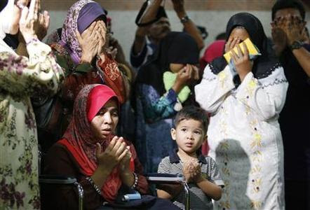 Noraziah Noor (seated L) and Nurunisa Abu Bakar (2nd R), the wives of Inspector Zulkifli Mamat and Corporal Sabarudin Daud respectively, who are the members of the Malaysian Police 69th Commando Battalion killed on Friday in the standoff between Malaysian security forces and armed followers of the Sultanate of Sulu, recite a prayer as they wait for the arrival of their bodies at an airport in Subang, outside Kuala Lumpur March 2, 2013. A standoff between Malaysian security forces and armed Filipinos ended in violence on Friday, with at least two police officers killed amid conflicting reports of casualties as Malaysian Prime Minister Najib Razak declared his patience had run out. Malaysian state news agency Bernama said that two police commandos had been killed in a mortar attack and two wounded after security forces tried to force out the group of at least 100 Filipinos who have been holed up in eastern Sabah state for more than two weeks. REUTERS-Bazuki Muhammad