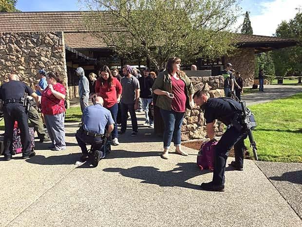 Policiais verificam mochila dos estudantes da Umpqua Community College depois que um atirador disparou no campus (Foto: Mike Sullivan/Roseburg News-Review via AP)