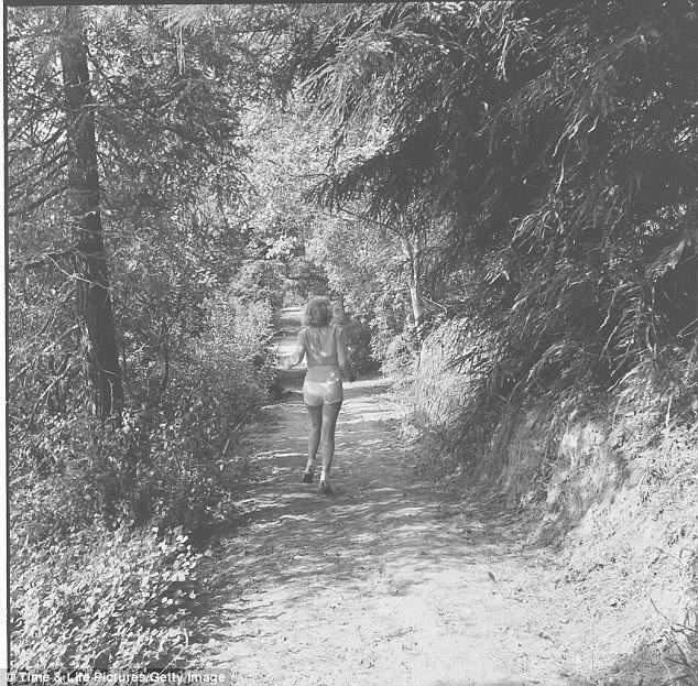 Longa e sinuosa estrada: Vestido em um shorts e camisa de cor clara, ela se afasta por um caminho parcialmente sombreados