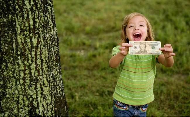 child holding $10 bill - kids savings account