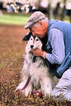 Old man hugging his old dog.