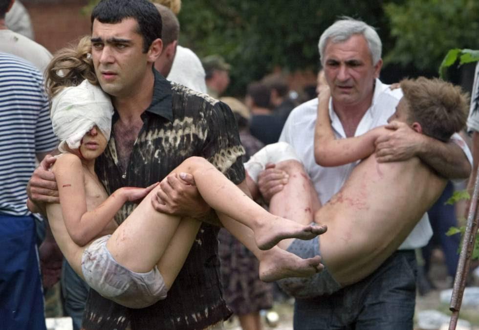Dos hombres llevan en brazos a sendos niños liberados tras el asalto de las fuerzas rusas en Beslan, en 2004 (archivo). rn