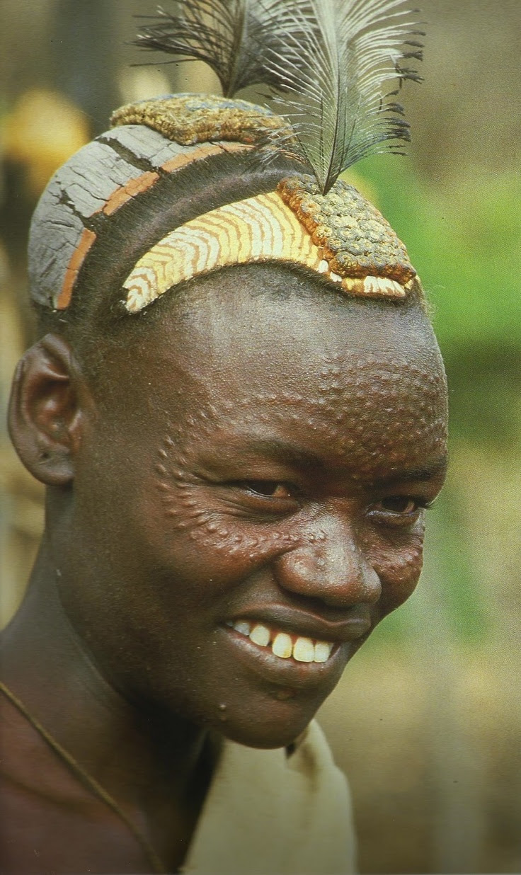"Africa | Bumi men scar their faces and wear multicoloured decorations made from clay which are often adorned with feathers | Image scanned from the publication ""Decorated Skin, a world survey of body art"" by Karl Gornin."