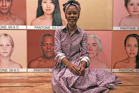 """Angelica Dass, a Brazilian artist who lives in Spain, poses at the entrance to her exhibition """"Humanae,"""" which is on view at the Health Museum through Sept. 5."""
