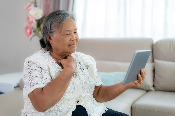 woman holding tablet computer and pointing to throat