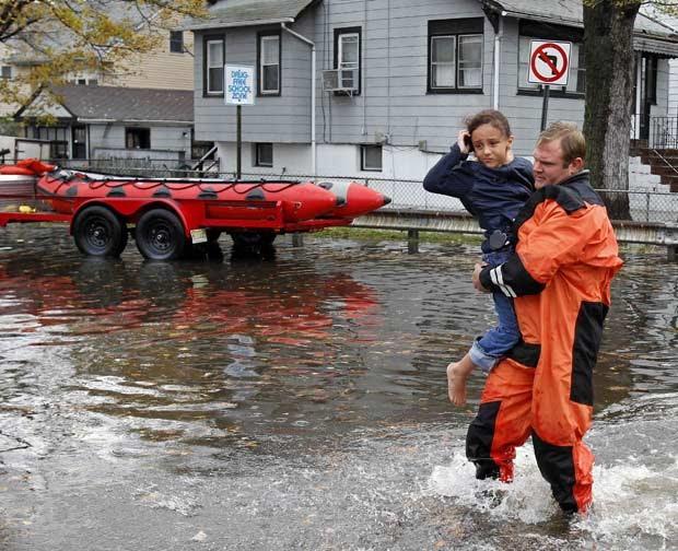 Resgatista carrega menina em rua alagada de Little Ferry, no estado americano de Nova Jersey, nesta terça-feira (30) (Foto: Reuters)