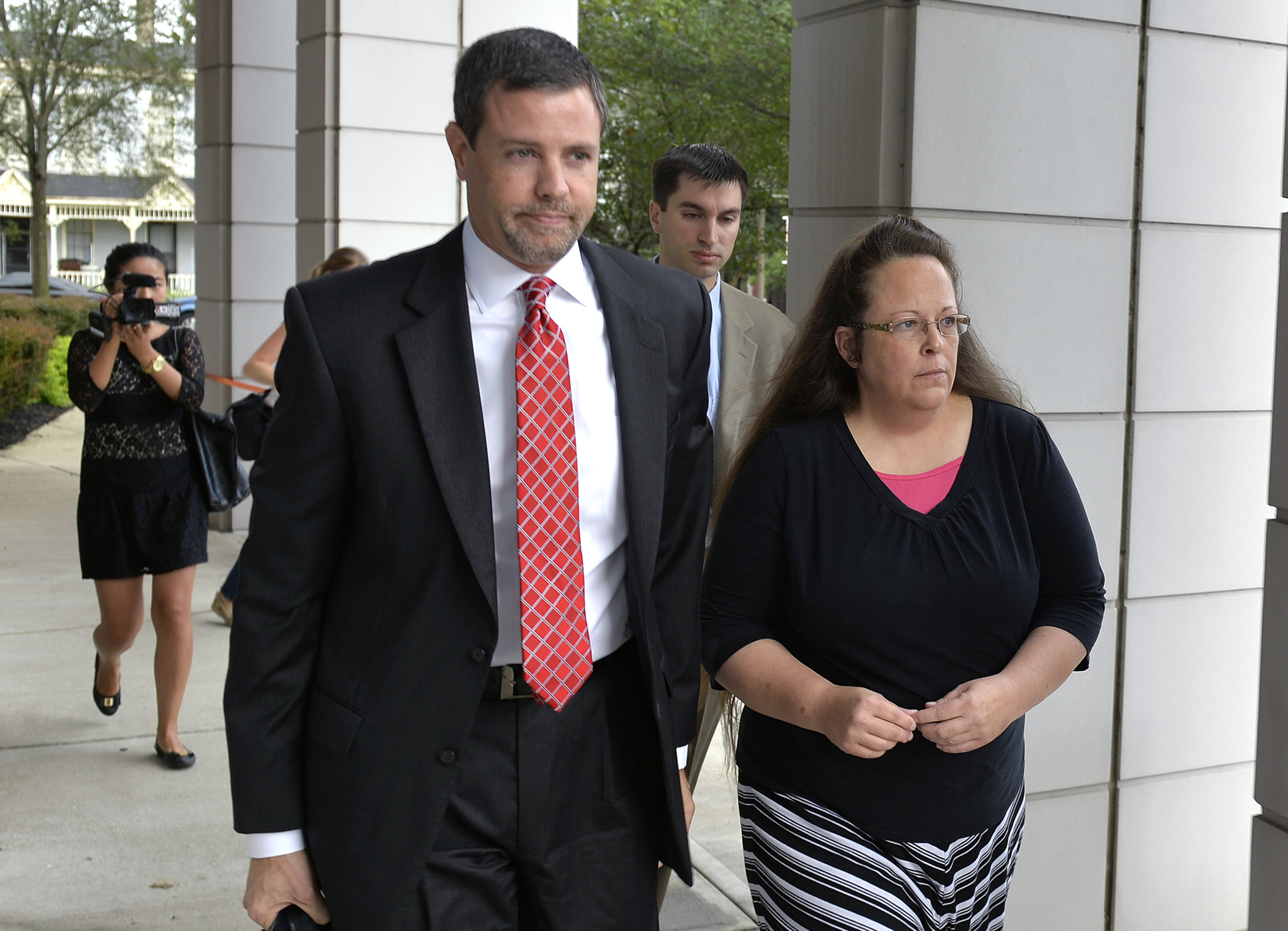 In this July 20, 2015 file photo, Rowan County Clerk Kim Davis, right, walks with her attorney Roger Gannam into the United States District Court for the Eastern District of Kentucky in Covington, Ky. The Rowan County, Ky., clerk's office turned away gay couples who sought marriage licenses on Thursday, Aug. 13, 2015, defying a federal judge's order that said deeply held Christian beliefs don't excuse officials from following the law. The fight in Rowan County began soon after the Supreme Court legalized gay marriage nationwide in June. Davis cited her religious beliefs and decided not to issue marriage licenses to any couple, gay or straight. (AP Photo/Timothy D. Easley)