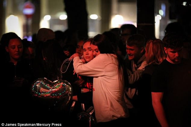 Mourners console each other as they attend vigils around Manchester to remember the murdered concertgoers