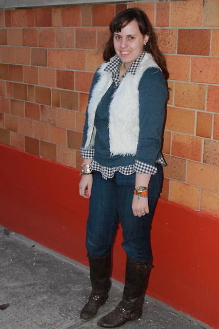 Layered outfit: thrifted fur vest, gingham shirt, straight-leg jeans, leather boots, bracelets, rose gold watch