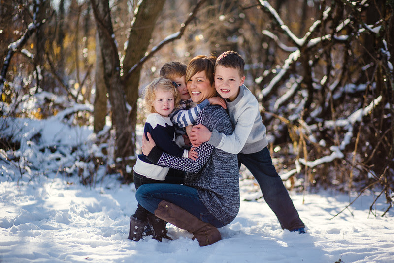 Pictures outside with a family of five with little boys and a little girl in the woods by a covered bridge with snowy backgrounds. The Harshbarger family had a fun time playing in the snow outside making for beautiful candid moments by Rockford IL Portrait Photographer, Mindy Joy Photographer.
