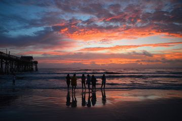 A group of Disney cast members watch the first sunrise of the new year by the Cocoa Beach Pier, Fla. A proposed bill would keep daylight-saving time year round in the state.
