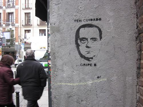 pintada callejera en la que se ve a Berlusconi sobre el letrero: cuidado, gripe B