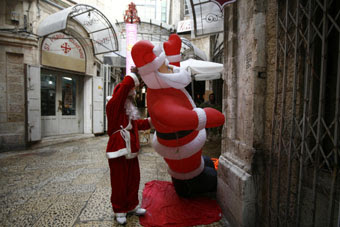 Reuters photo,  Baz Ratner - A man wearing a Santa Claus costume places an inflatable Santa Claus doll in an alley in Jerusalem's Old City ahead of Christmas (December 22, 2010)