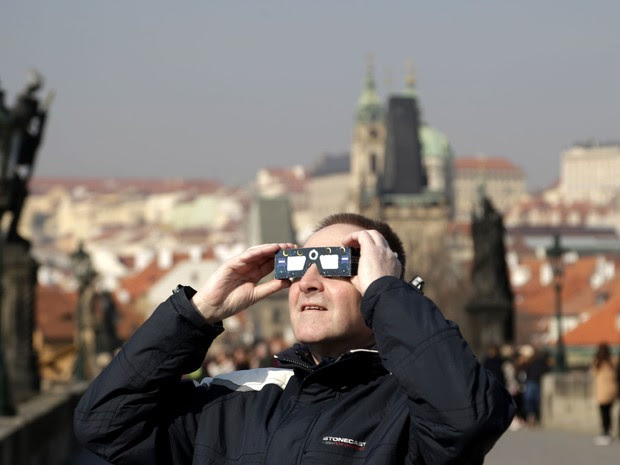 Homem tenta observar eclipse solar em Praga, na República Tcheca, nesta sexta-feira (20) (Foto: Petr David Josek/AP)