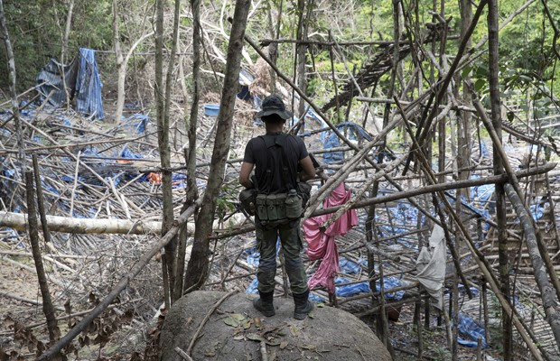 Policial observa acampamento abandonado por supostos traficantes de pessoas numa floresta da Malásia (Foto: Damir Sagolj/Reuters)