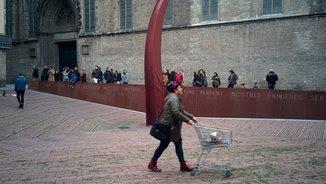 Una dona enretira una dels carros de la instal·lació al fossar de les Moreres (Joan Llacuna)