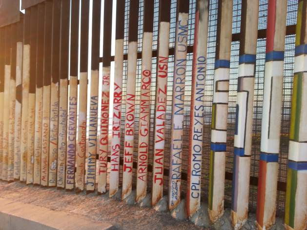 Names of migrants who died crossing, on U.S.-Mexico border fence, Tijuana. Credit: Peter Costantini