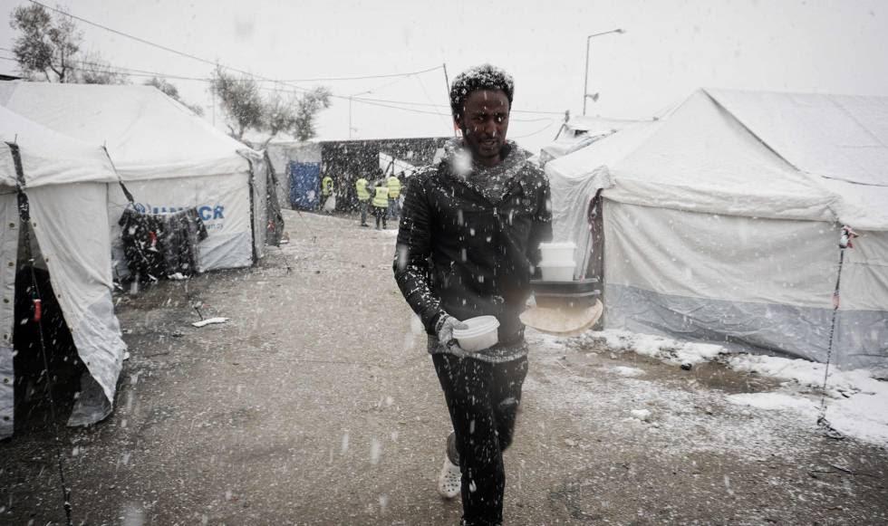 Un migrante del campamento de Moria, en la isla griega de Lesbos, caminaba ayer hacia su tienda con un recipiente de comida.