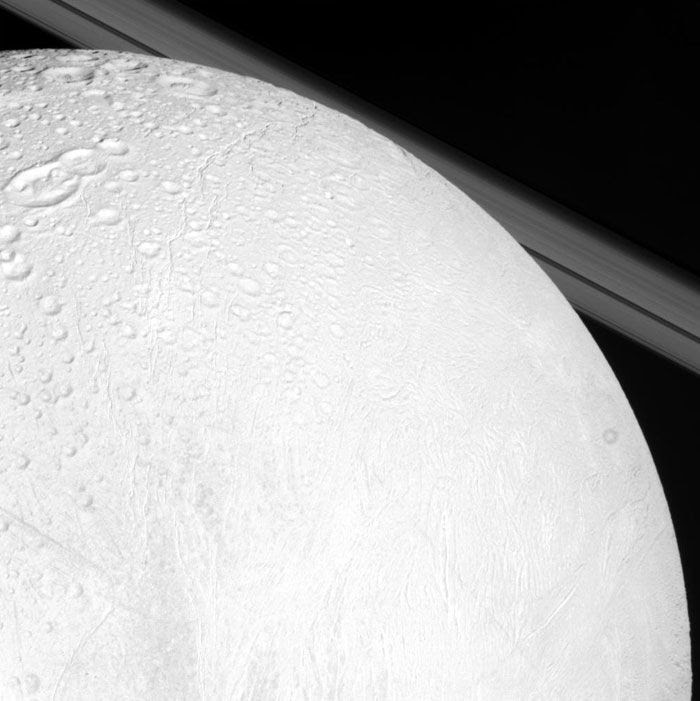 An image, taken by NASA's Cassini spacecraft, of Saturn's moon Enceladus with the planet's rings in the background.