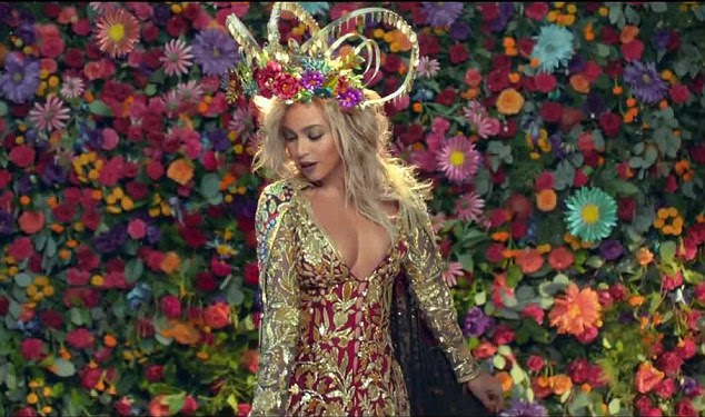 A wall of colour: Filmed in Mumbai, India, the video sees the R&B icon look stunning in traditional Indian attire while she provides ethereal vocals to complement Chris Martin's