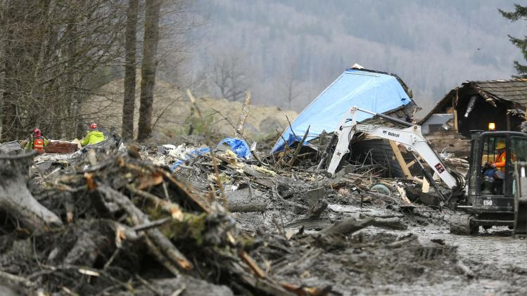 Workers dig through debris in the mudslide near Oso