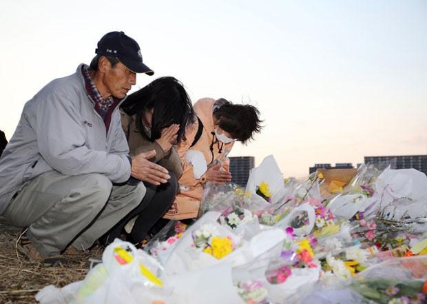 Pessoas rezam para Ryota Uemura, adolescente de 13 anos que foi encontrado degolado em Tóquio, no Japão, nesta sexta-feira (27). Outros três jovens foram presos pelo crime. (Foto: Jiji Press/AFP)