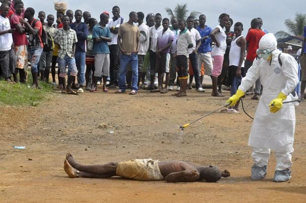Funcionário de departamento de saúde da Libéria limpa com desifetante um homem que teria morrido por ebola em Monrovia. A imagem é de 4 de setembro (Foto: Abbas Dulleh/AP)